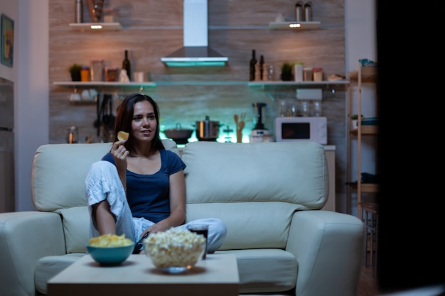 Attente geconcentreerde jongedame die naar film kijkt en snacks eet