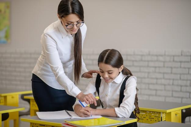Attente geïnteresseerde vrouw in glazen bukken lachend schoolmeisje schrijven aan haar bureau