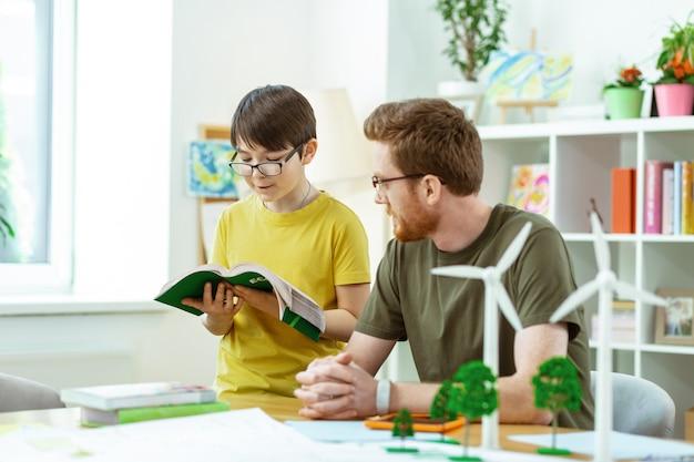 Attente gember man. geconcentreerde kortharige bebaarde leraar die zijn student helpt terwijl hij zelfstudie leest