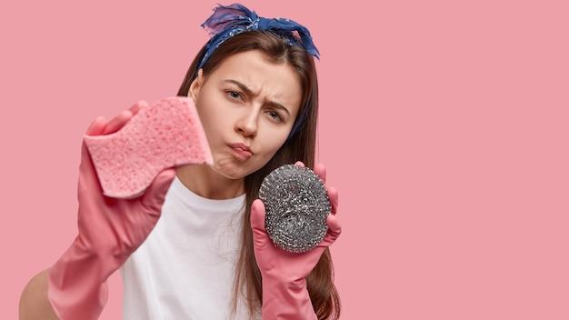 Attente huisvrouw kijkt nauwgezet naar de camera, maakt vuil oppervlak schoon met een spons, draagt rubberen handschoenen