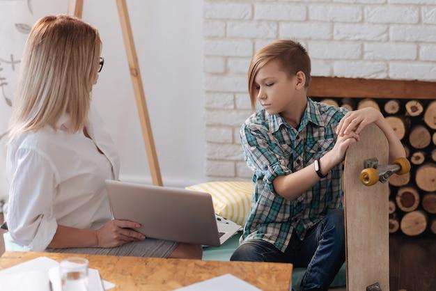 Attente jongen die vrijetijdskleding draagt die dichtbij vrouw zit die op laptop kijkt