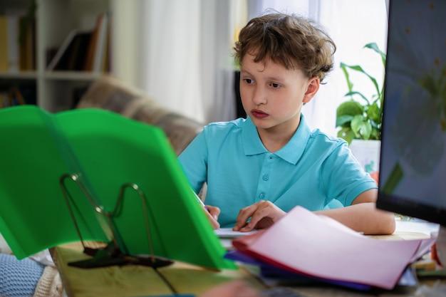 Attente jongen schooljongen zitten aan tafel en huiswerk, handboek kijken