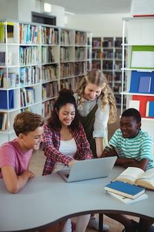 Attente klasgenoten met laptop in bibliotheek