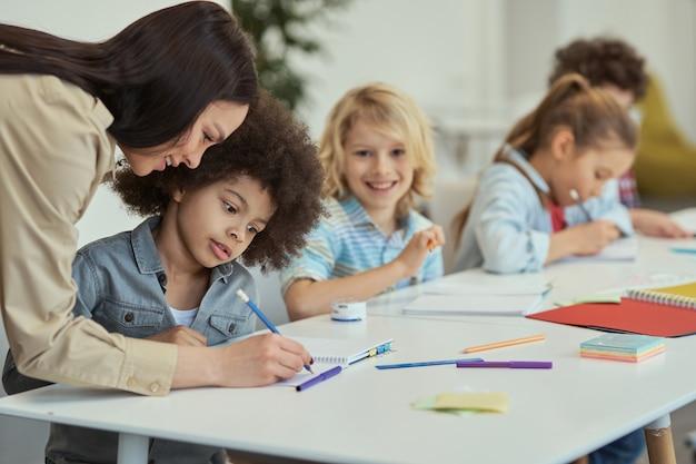 Attente kleine schooljongen die naar de vrouwelijke leraar luistert terwijl hij aan de tafel zit in het basisonderwijs