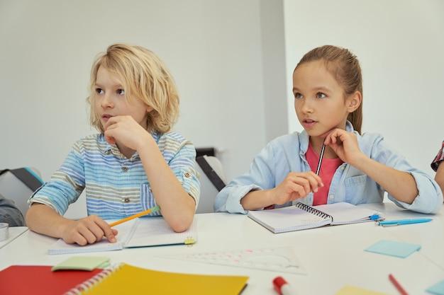 Attente kleine schooljongen en schoolmeisje studeren en luisteren naar de leraar die samen aan de zit