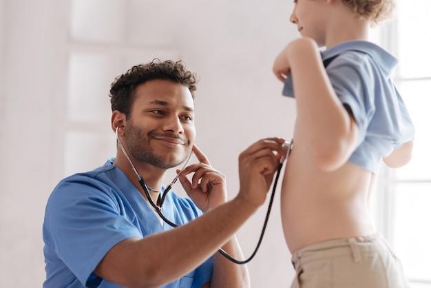 Attente mannelijke persoon in speciaal uniform met behulp van een stethoscoop tijdens het controleren van het hart van zijn jonge patiënt