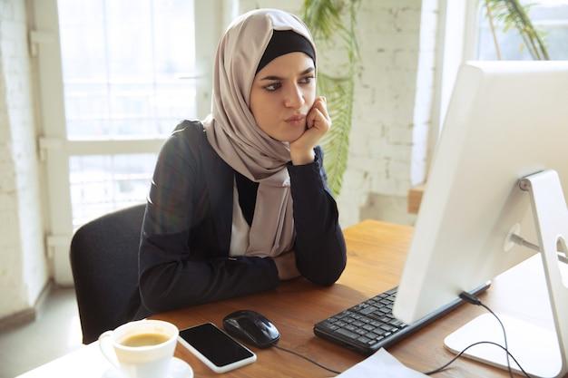 Attente moslimvrouw die met computer werkt