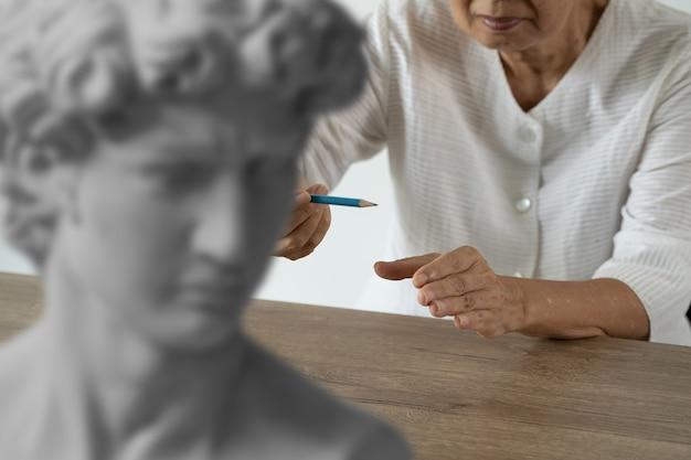 Attente oudere vrouw kunst en beeldhouwkunst plezier bij de creatieve workshop vrouw schilderen