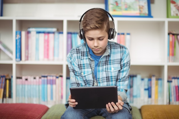 Attente schooljongen luisteren muziek tijdens het gebruik van digitale tablet in bibliotheek