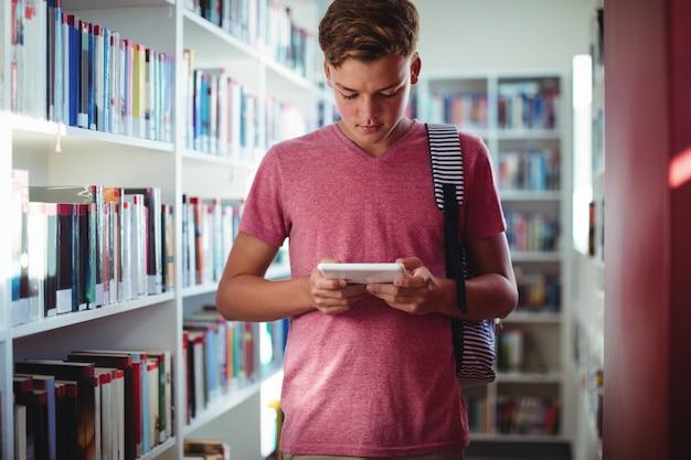 Attente schooljongen met behulp van digitale tablet in bibliotheek