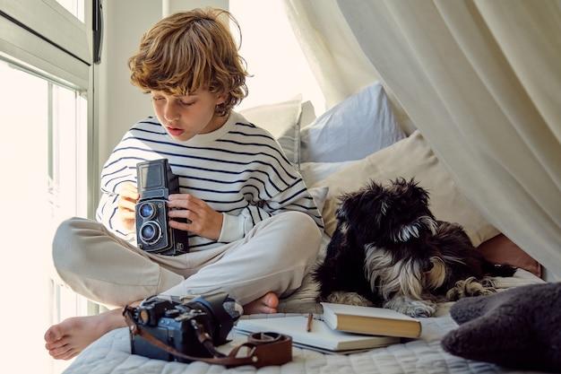Attente schooljongen met vintage fotocamera in de buurt van hond op bed