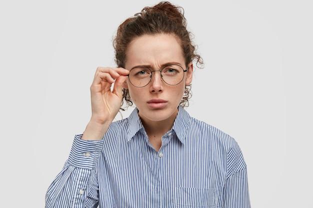 Attente sproeten tiener met bril poseren tegen de witte muur