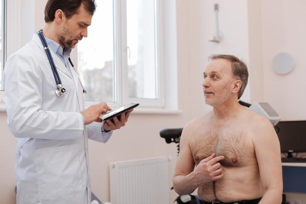 Attente verantwoordelijke senior gentleman die sommige dingen aan zijn arts uitlegt terwijl hij aandachtig luistert en ze opschrijft