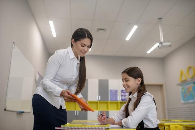 Attente vrouw met lang donker haar tablet tonen aan geïnteresseerd schoolmeisje achter haar bureau