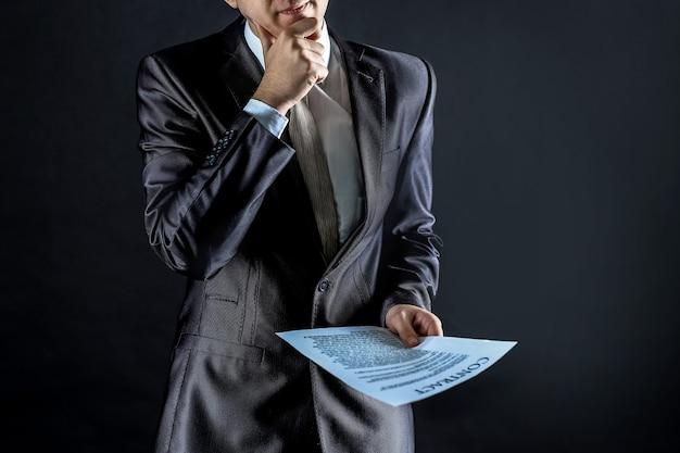 Attente zakenman overweegt de voorwaarden van een nieuw contract. geïsoleerd op zwarte achtergrond