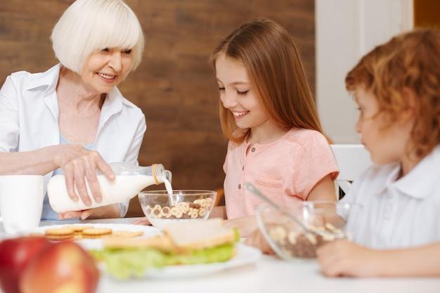 Attente, zorgvuldige oudere vrouw die melk in de kom met ontbijtgranen giet tijdens het bereiden van een maaltijd voor de kinderen die haar in het weekend bezoeken
