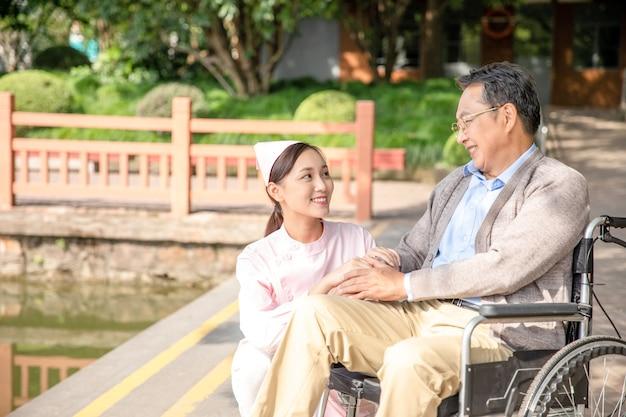 Attentie van een verpleegster met een oude man in een rolstoel