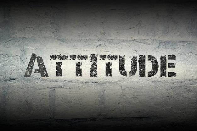 Attitude stencildruk op de grunge witte bakstenen muur
