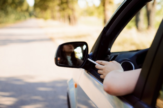 Attracive blanke vrouw rokende sigaret tijdens het besturen van een auto op de weg