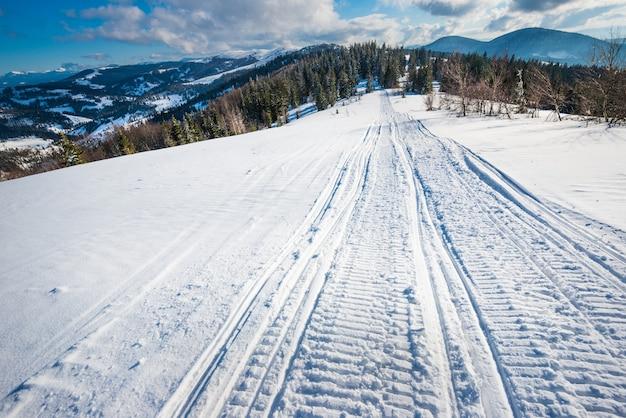 Atv- en ski-tracks in de sneeuw op een zonnige ijzige winterdag