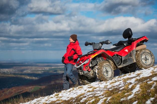 Atv quad in de buurt van man op besneeuwde berghelling
