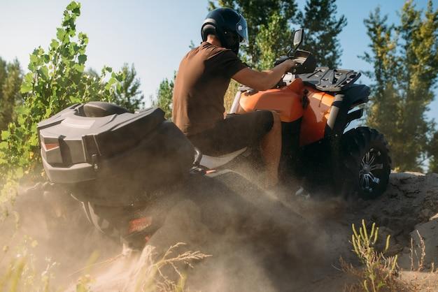 Atv-rijder die de zandberg beklimt, achteraanzicht