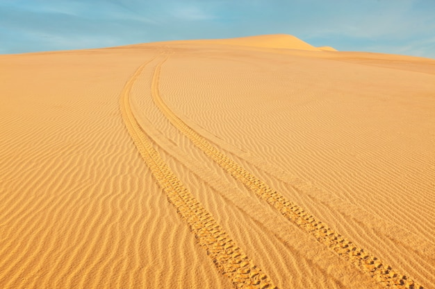 Atv-terreinvoertuigen voor elk terrein in witte zandduinen bij zonsopgang,