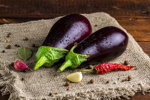 Aubergine, droge, rode peper, knoflook, laurierbladeren op een houten achtergrond. aubergine gewas