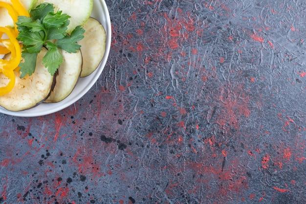 Aubergine en paprika plakjes met een kleine peterselie bundel op een schotel op zwarte tafel.