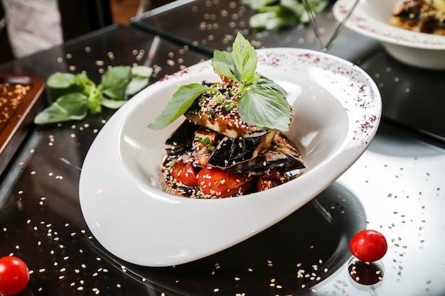 Aubergine en tomaten gegarneerd met sesamzaadjes