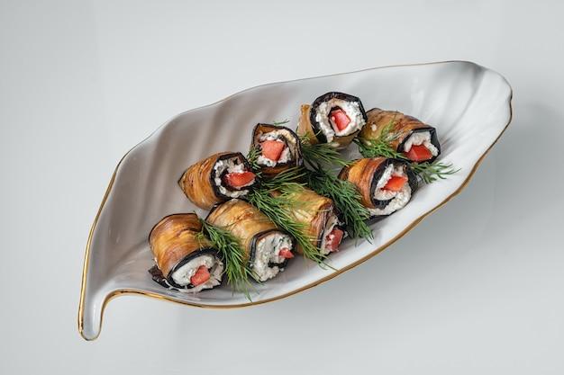 Auberginebroodjes met kwark en tomaat met dilletakken op een decoratief wit bord in de