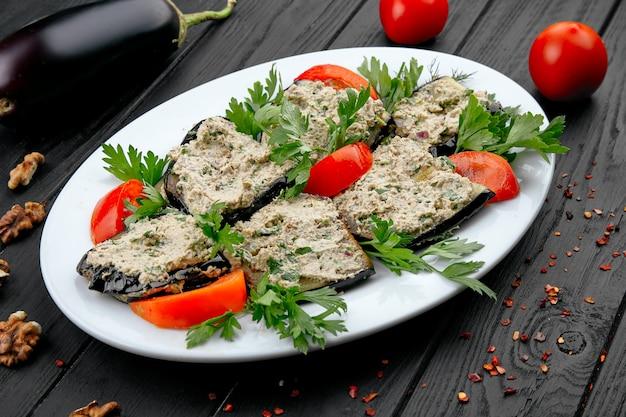 Auberginerolletjes met tomaat. traditionele georgische snack. veganistisch eten op donkere houten achtergrond. gezond, dieet voedsel concpet met kopie ruimte.