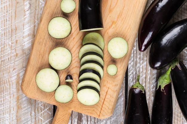 Aubergines en gehakte op een snijplank en houten