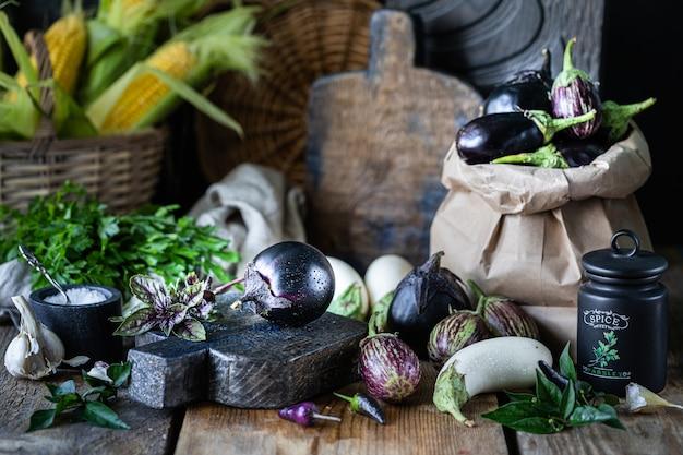 Aubergines van verschillende kleuren en verschillende kwaliteiten op een houten tafel.