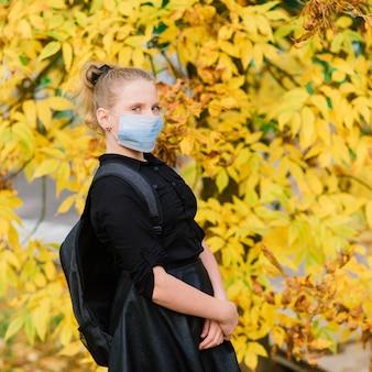 Aucasian schoolmeisje tiener in een medisch masker dat het gezicht beschermt op de achtergrond van een herfstlandschap