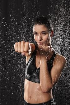? aucasische atletische vrouw die zwarte sportieve bh punchning met gebalde vuist draagt, die over de achtergrond van regendalingen wordt geïsoleerd