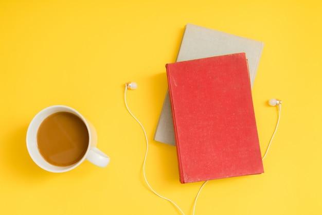 Audio boek concept. hoofdtelefoons, koffie en hardcoverboek over gele lijst.