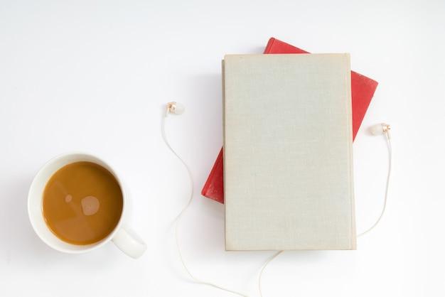 Audio boek concept. koptelefoon, koffie en boek met harde kaft boven tafel.