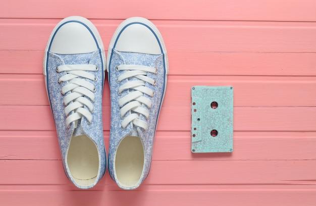 Audio cassette en sneakers schoenen op een roze pastel achtergrond. ouderwetse technologieën. bovenaanzicht plat liggen.