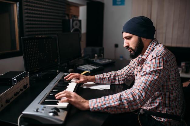 Audio engineering, geluidsman werkt met synthesizer in studio. professionele digitale geluidsopnametechnologie