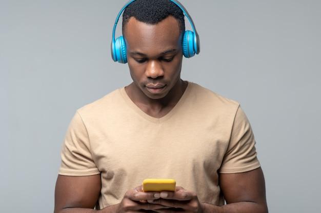Audio, luisteren. jonge volwassen donkere man in lichtblauwe koptelefoon aandachtig kijken naar scherm van gele smartphone in zijn handen