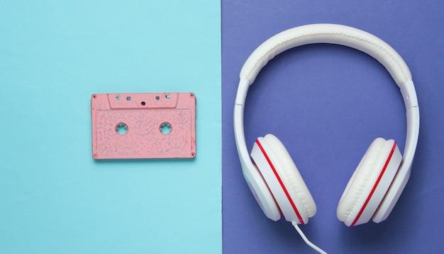 Audiocassette en koptelefoon op paars blauwe achtergrond. retro muziekconcept. uitstekende achtergrond. discofeestje. bovenaanzicht