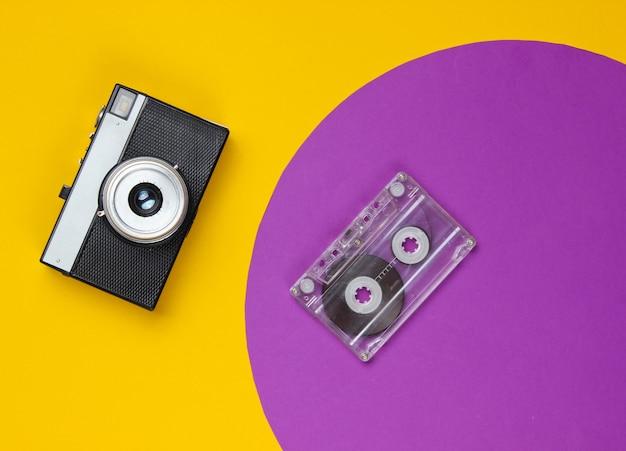 Audiocassette en retro filmcamera op geel met paarse cirkel