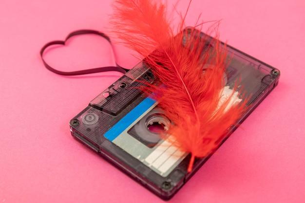 Audiocassetteband op roze achtergrond. filmvormend hart, valentijnskaart. lege ruimte.