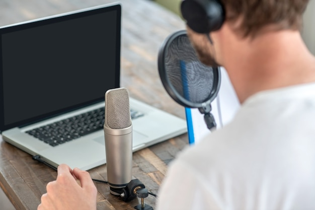 Audioconferentie. een jonge man die in de microfoon spreekt en er betrokken uitziet