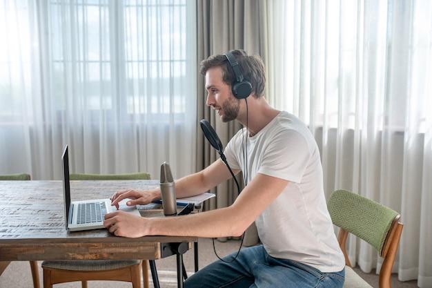 Audioconferentie. jonge, bebaarde man die in een koptelefoon zit en een audioconferentie heeft