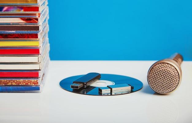 Audiomicrofoon met cd's en een flashstation op een houten tafel