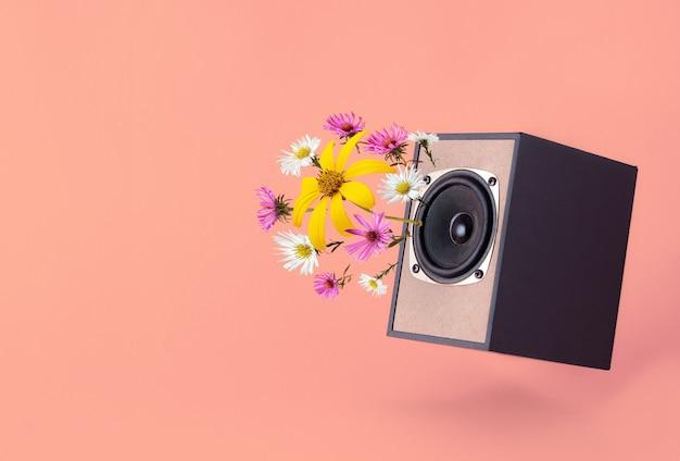 Audiospreker met lentebloemen op koraalachtergrond. minimaal lentevibe-concept. geluiden van de lente en frisse ideeën.