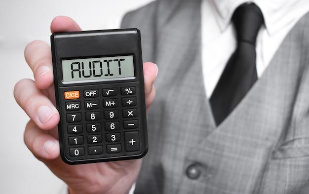 Audit woord tekst inscriptie op rekenmachine in een mannenhand van een zakenman in wit overhemd en blauwe stropdas