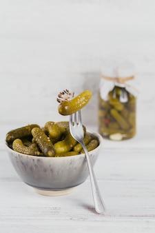 Augurken, ingelegde komkommer op een vork, kom gemarineerde groenten op witte houten achtergrond. schoon eten, vegetarisch voedselconcept